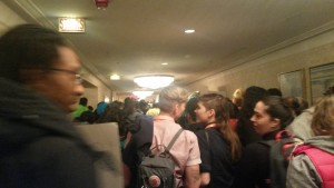Slightly blurry photo of a hotel hallway, with a crowd of people of different races, seen from behind, some holding signs, with the crowd extending forward as far as one can see in the picture