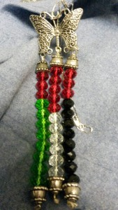 Three colored strings of beads, with the colors making a Palestinian flag, hang from a metal figure of a butterfly.