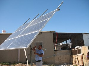 A middle-aged man with very short black hair and brown skin gestures to a solar panel in front of a ramshackle house.