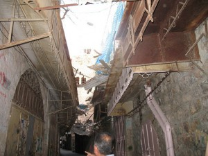 A deserted, very narrow, marketplace street, with stone shops. Some of their doors are vandalized and a net across the street between the roofs is straining from the chunks of debris in it.