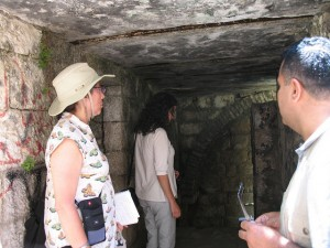 A young woman with brown skin, curly black hair, jeans, and a t-shirt, gazes at the wall inside an old stone room, while two other people look from behind her.