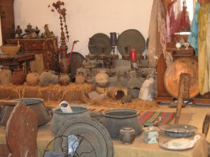 A display of battered old clay, copper, and stone dishes, vases, and other objects, and colorful stretches of cloth.