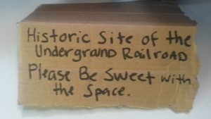 "Cardboard sign with the text ""Historic Site of the Underground Railroad. Please Be Sweet with the Space."""