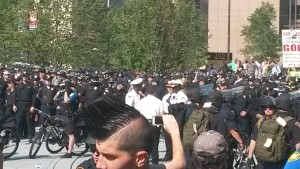 Several hundred police officers in various uniforms, some with bikes and some without, mill around a public park