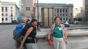 "A white female-presenting person, wearing a green ""social justice cleric"" shirt and a vest with first aid markings, smiles for a photo in a park, while a South Asian man in black, also with first aid markings, jumps into the photo making a funny face"